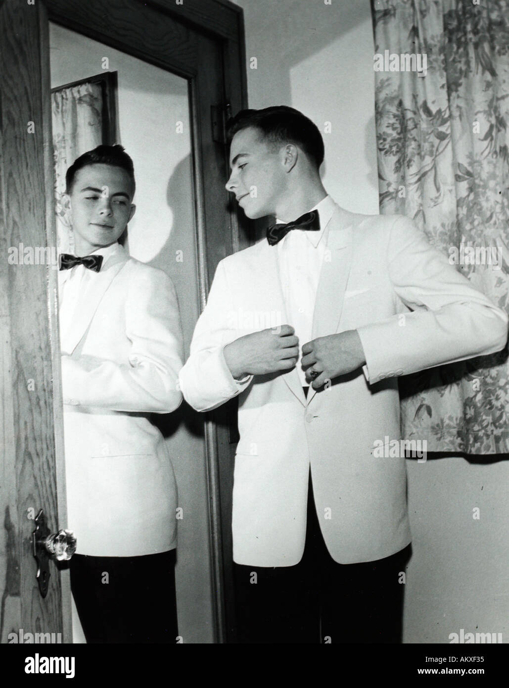 A teenage boy in a white tuxedo looking admiringly and confidently in mirror in 1950 s - Stock Image