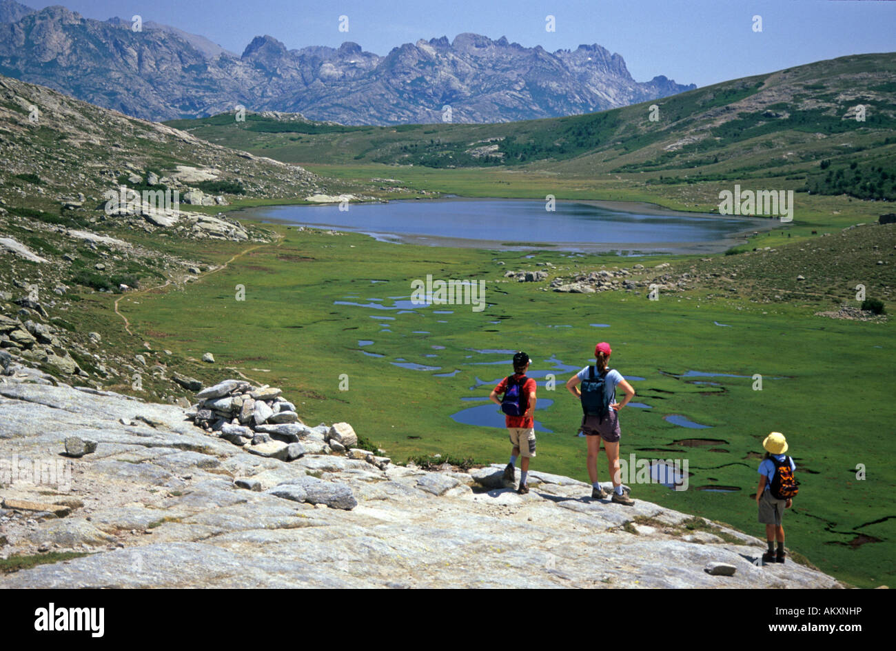 Hikers at the lake de Nino along the trekking route GR 20; Corse, France - Stock Image