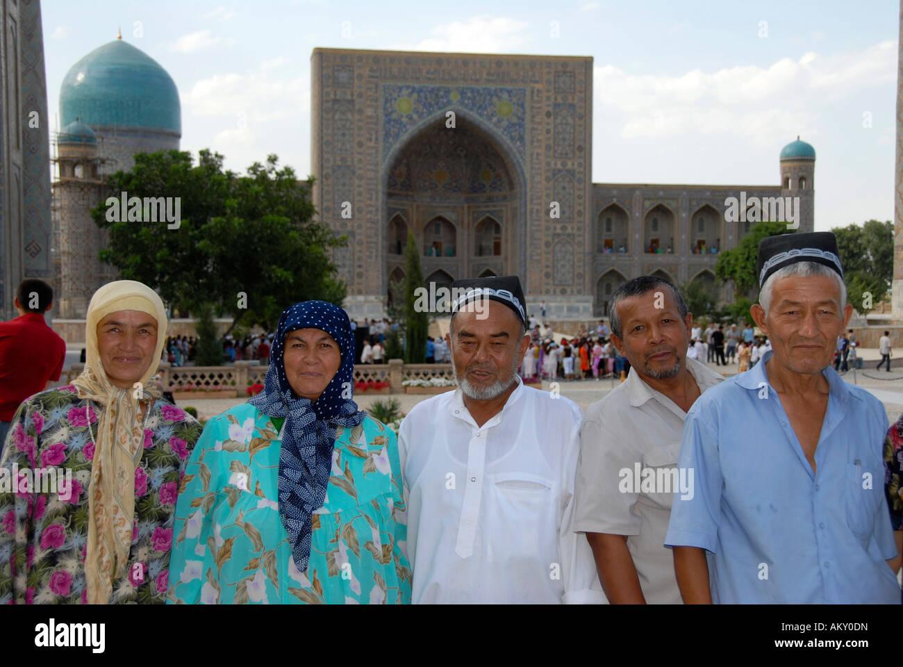 Uzbek people dressed in traditional cloth in front of Registan Madrasah Tilla-Kari Samarkand Uzbekistan - Stock Image
