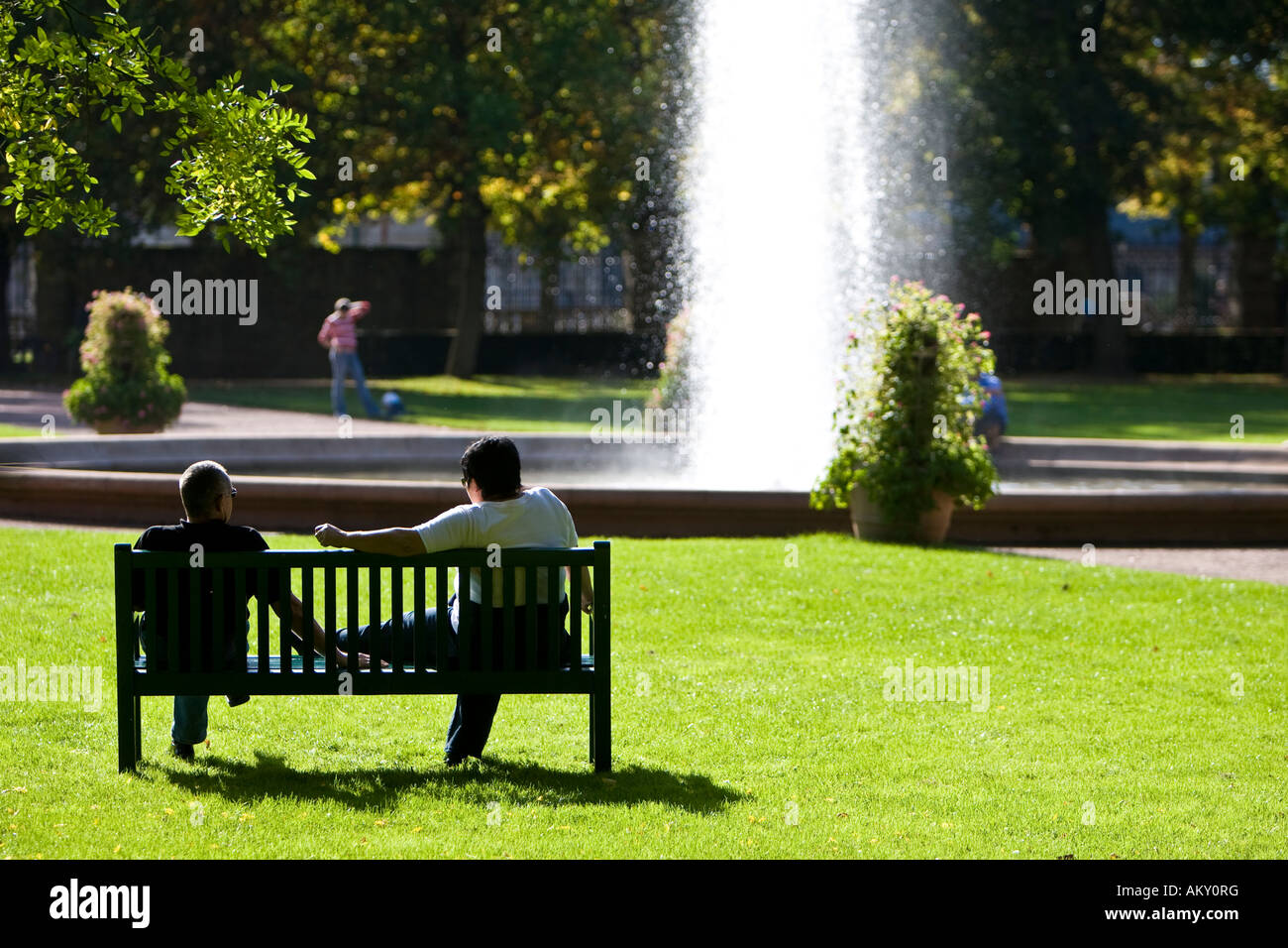 People In A Park Sitting On A Bench In Front Of A Fountain Hesse