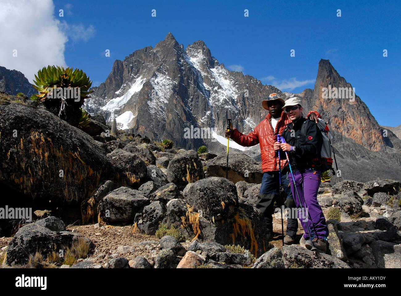 Mountaineerers among rocks below snow covered summit Batian (5199 m) Mount Kenya National Park Kenya - Stock Image