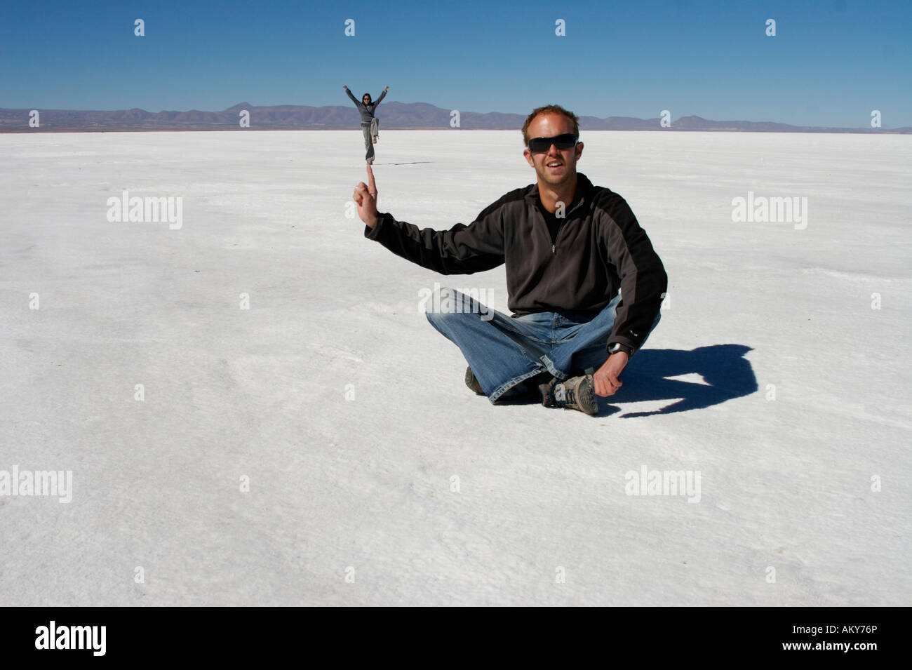 camera trick. illusion. balancing on my finger salar de uyuni salt plains bolivia - Stock Image