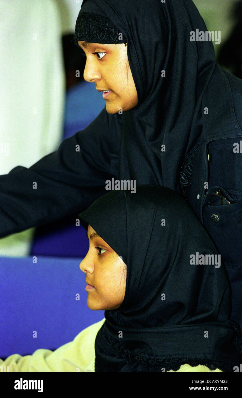 Two young Muslim women learning computer skills London UK Stock Photo