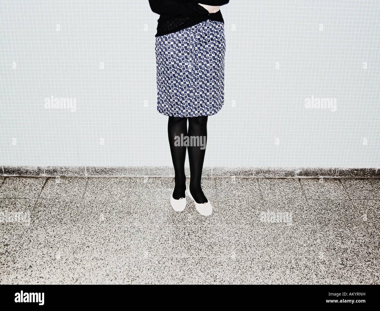 Young Woman With Chequered Skirt Standing In Front Of Wall Of Blue Tiles Berlin Germany - Stock Image