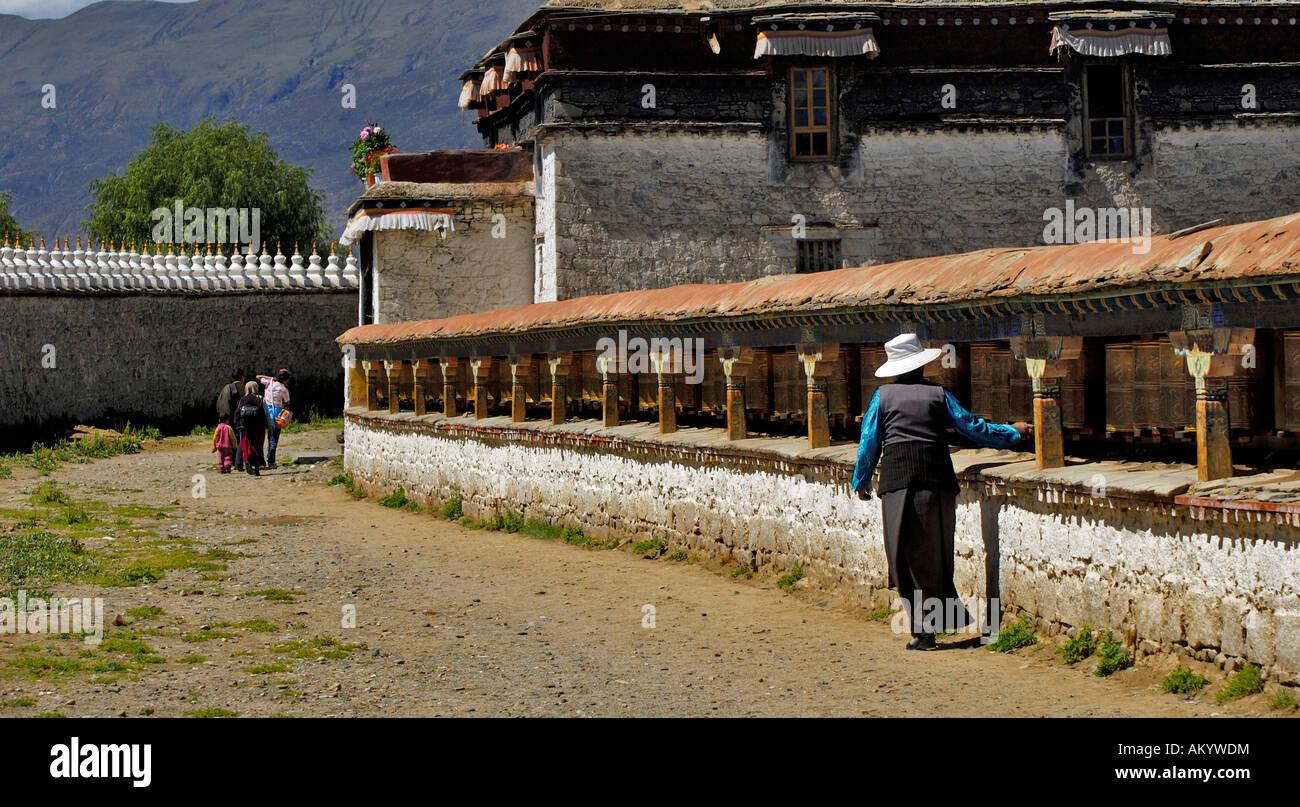 Old woman rotates the prayer mills, Samye monastery near Lhasa, Tibet, Asia - Stock Image