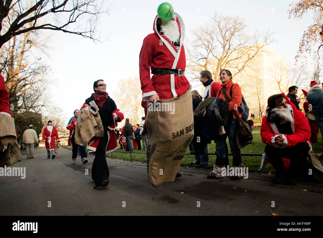 Students disguised as santa claus doing a sack-race, Dresden, Saxony, Germany - Stock Image