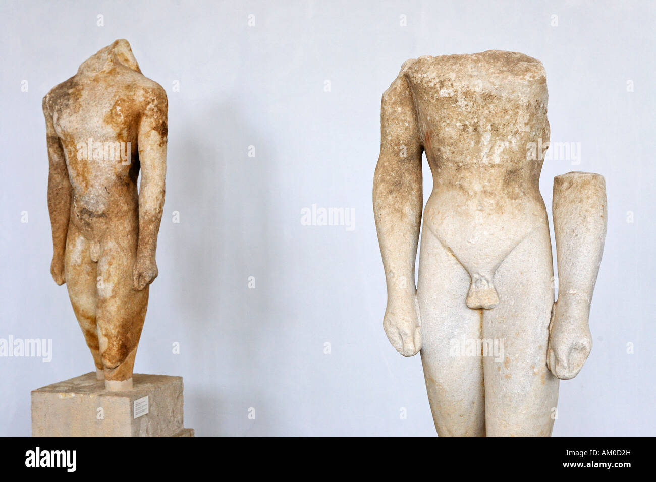 Statues of Kouroi on the left A 1742 on the right A 4048 made by craftsmen from Naxos 550 BC in Museum, Delos, Greece - Stock Image