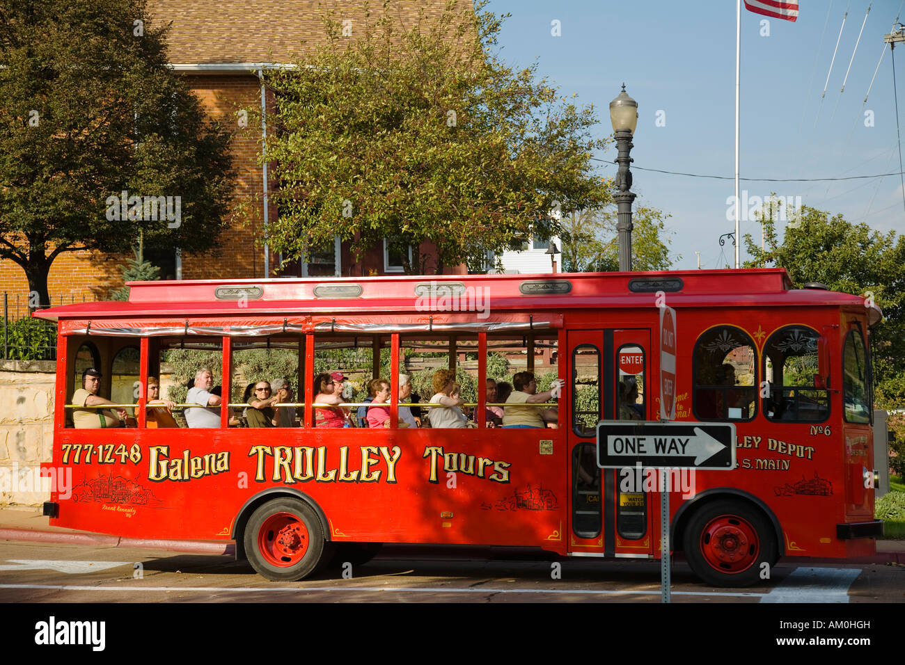 ILLINOIS Galena Tourists ride in open air red trolleys visit historic sites and locations in city open way street - Stock Image