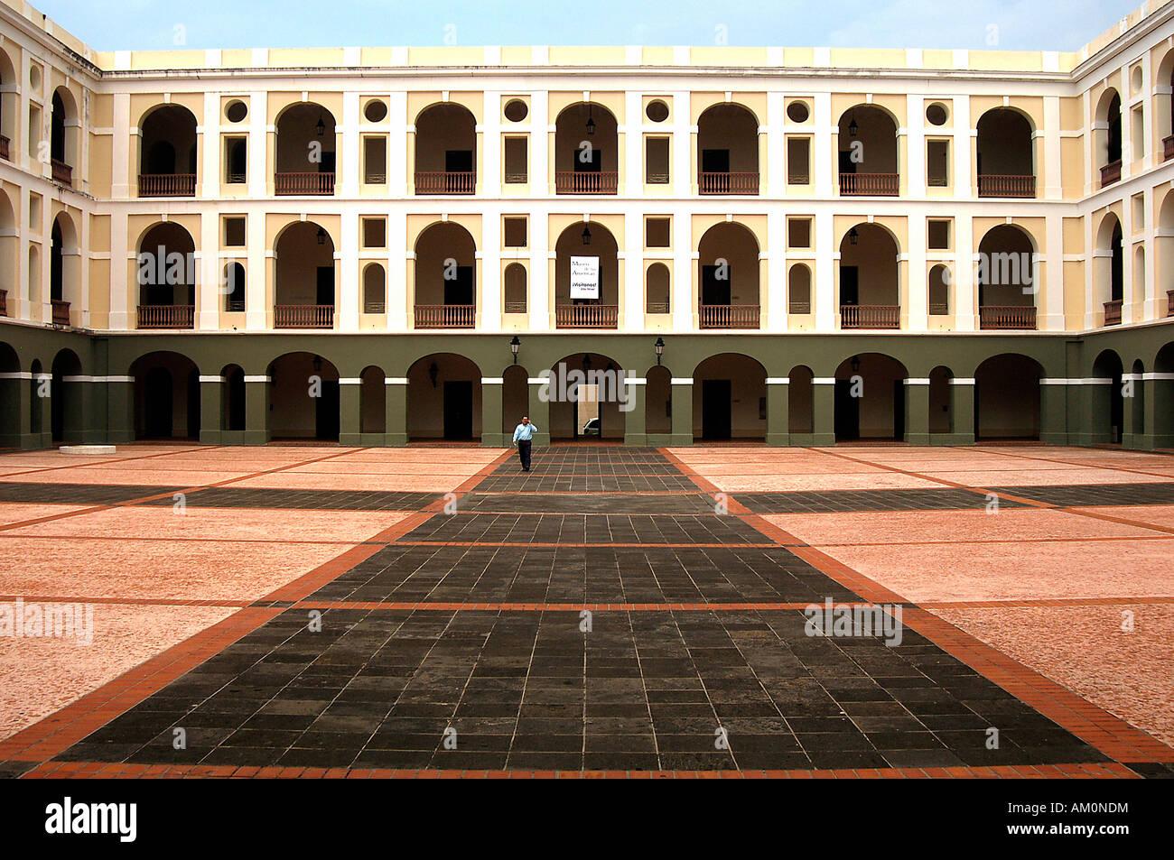 A man walks through the courtyard of the Cuartel de Ballaja in Puerto Rico's Old San Juan. - Stock Image
