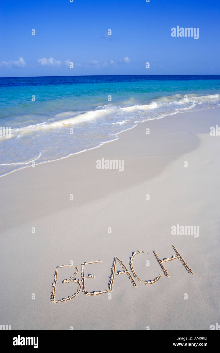 The word BEACH written on the sand on white tropical beach in Playa del Carmen, Cancun, Mexico - Stock Image