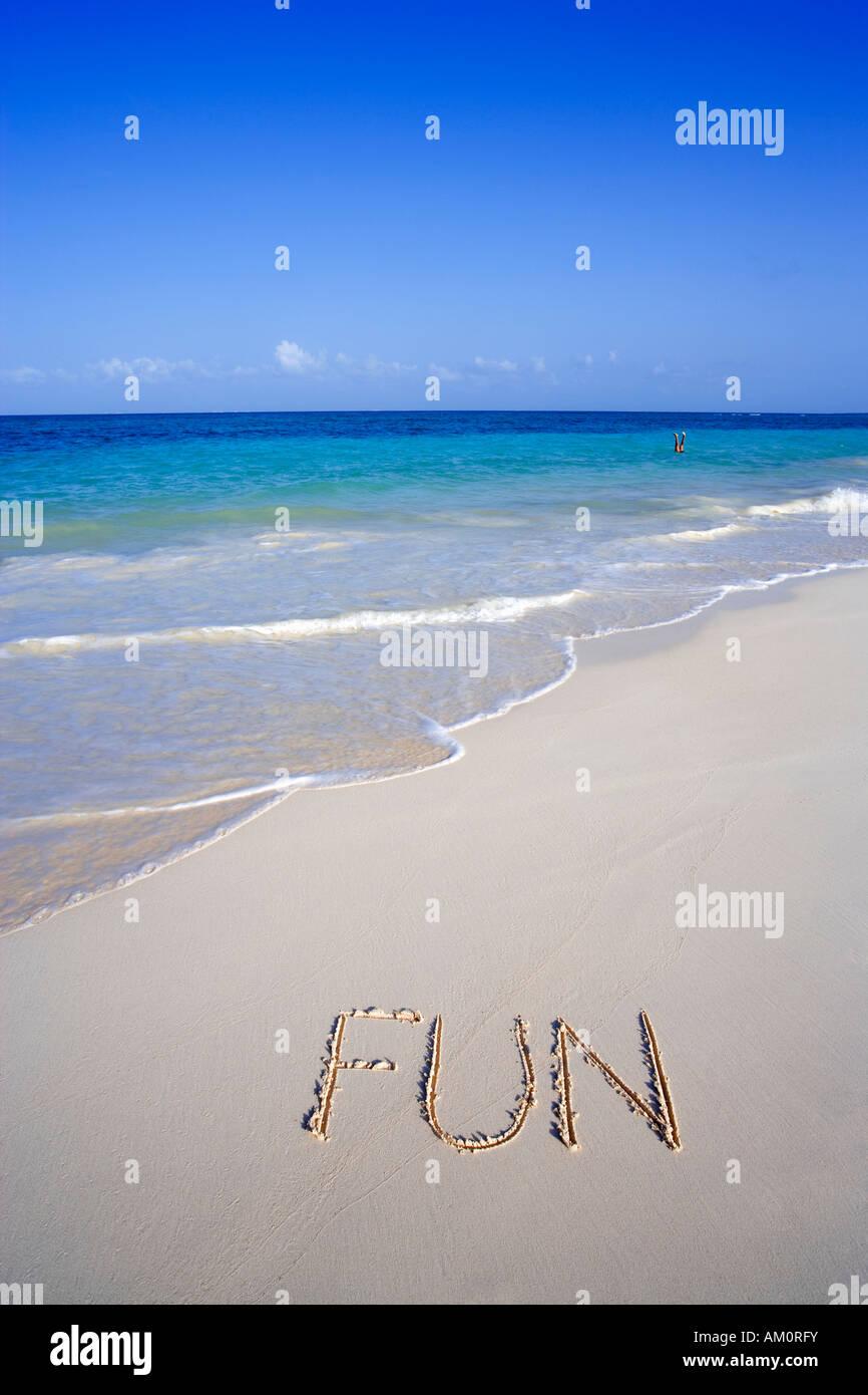 The word FUN written on white tropical beach in Playa del Carmen, Cancun, Mexico - Stock Image