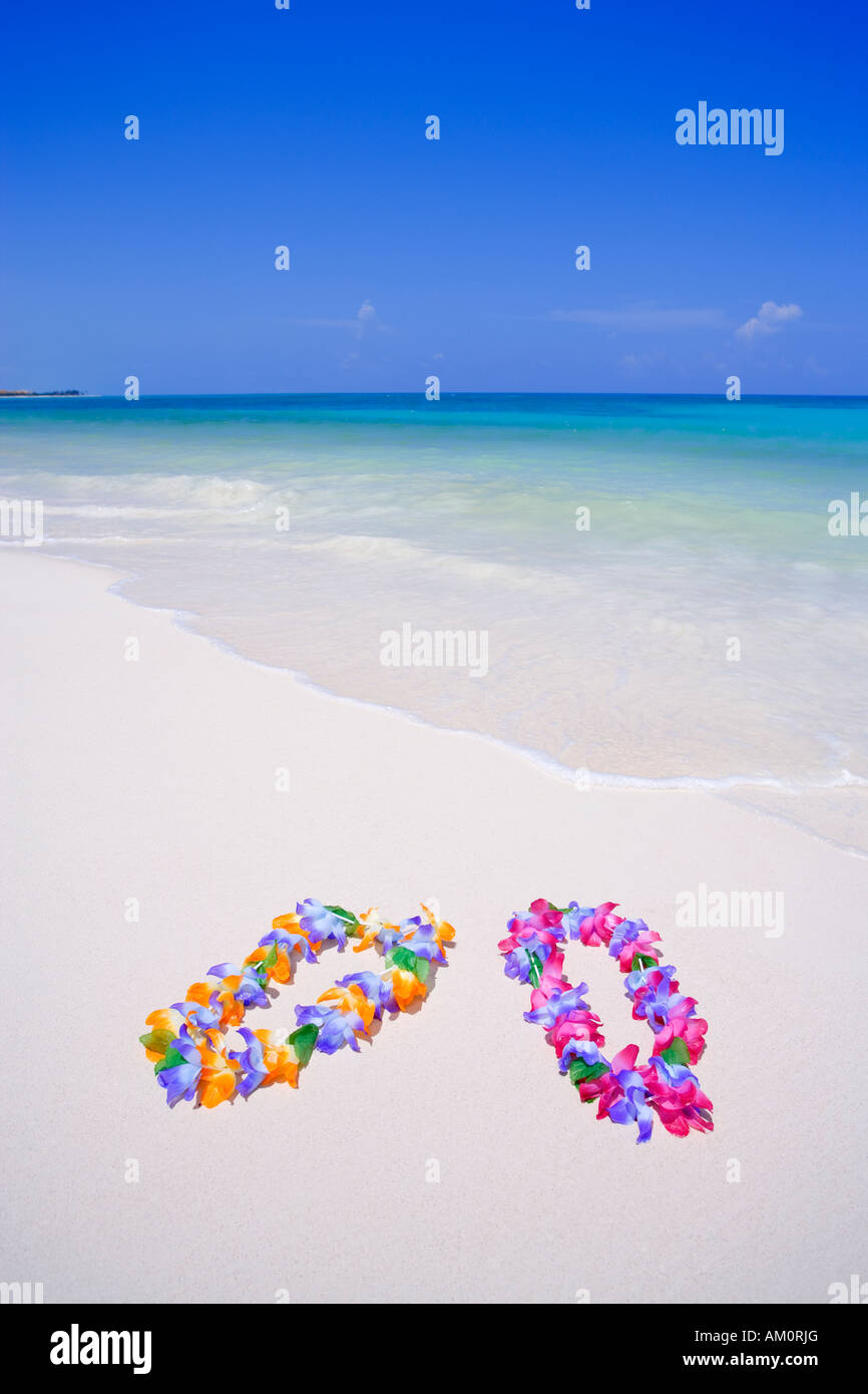 Two colorful floral lei necklaces on white tropical beach in Playa del Carmen, Riviera Maya, Mexico - Stock Image