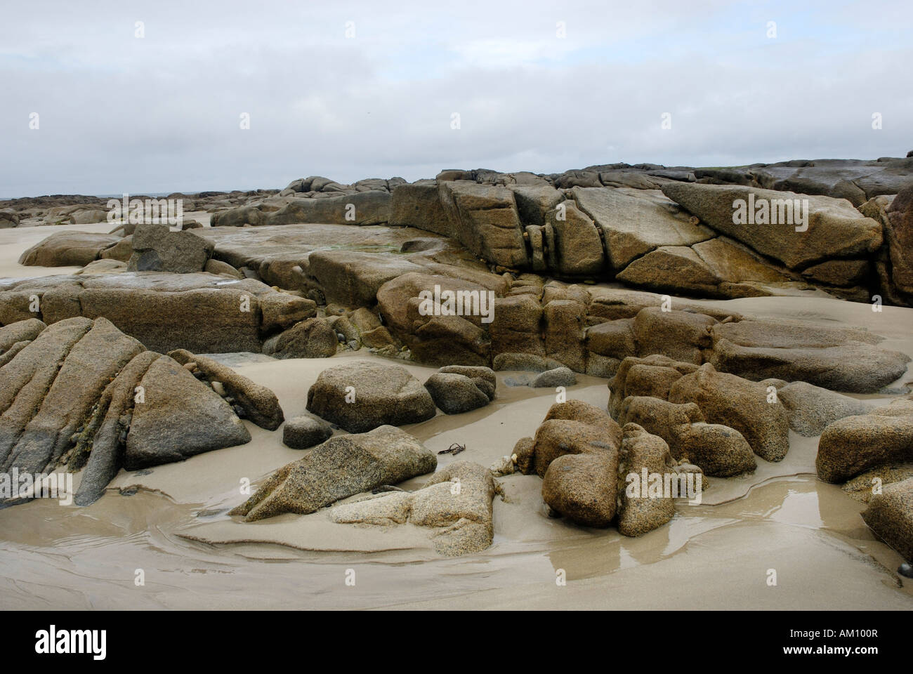 Granite rocks in tidal zone of sandy beach at the Altanic coast of Donegal on a foggy day, Ireland Stock Photo