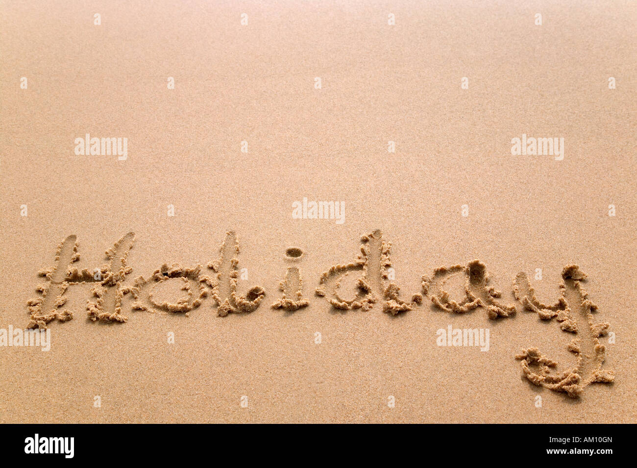 The word Holiday written in sand at the beach - Stock Image