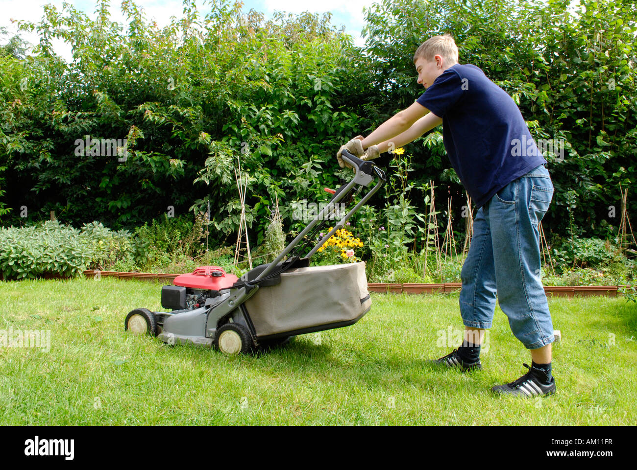 Teenager mowing lawn - Stock Image