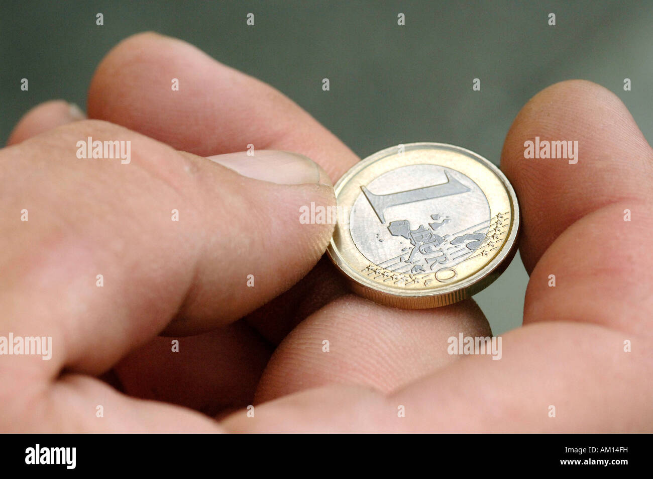 Hand with one Euro coin Stock Photo