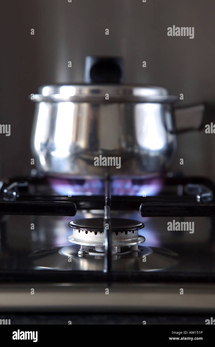 Close up of a gas hob with a pan on the back burner shallow DOF - Stock Image