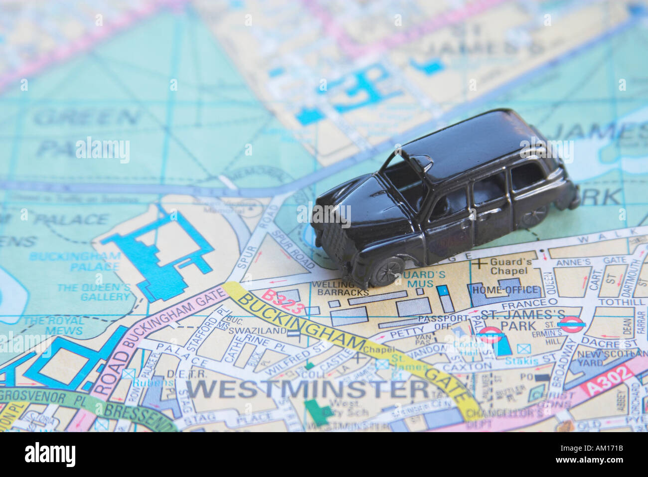 Black cab taxi on map of London England Britain United Kingdom UK - Stock Image