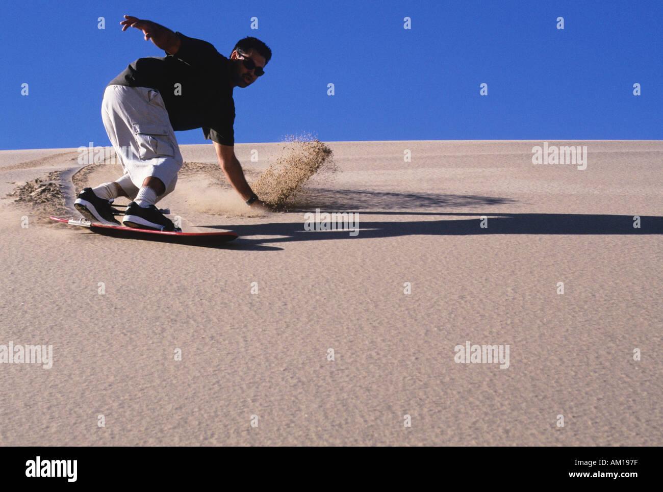 Sandboarding on a sand dune in the desert - Stock Image