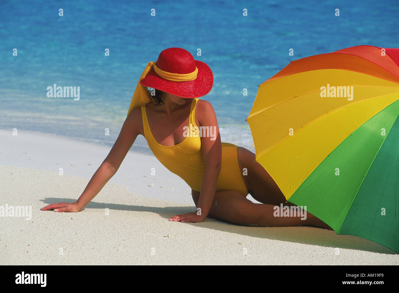 d093be154be Woman with red hat and colorful umbrella on sandy beach - Stock Image