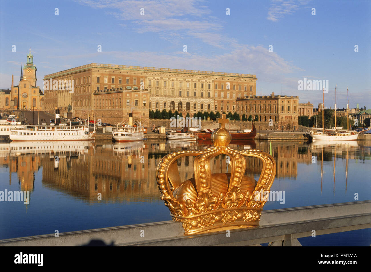Golden crown on Skeppsholmen Bridge with Royal Palace in Stockholm - Stock Image
