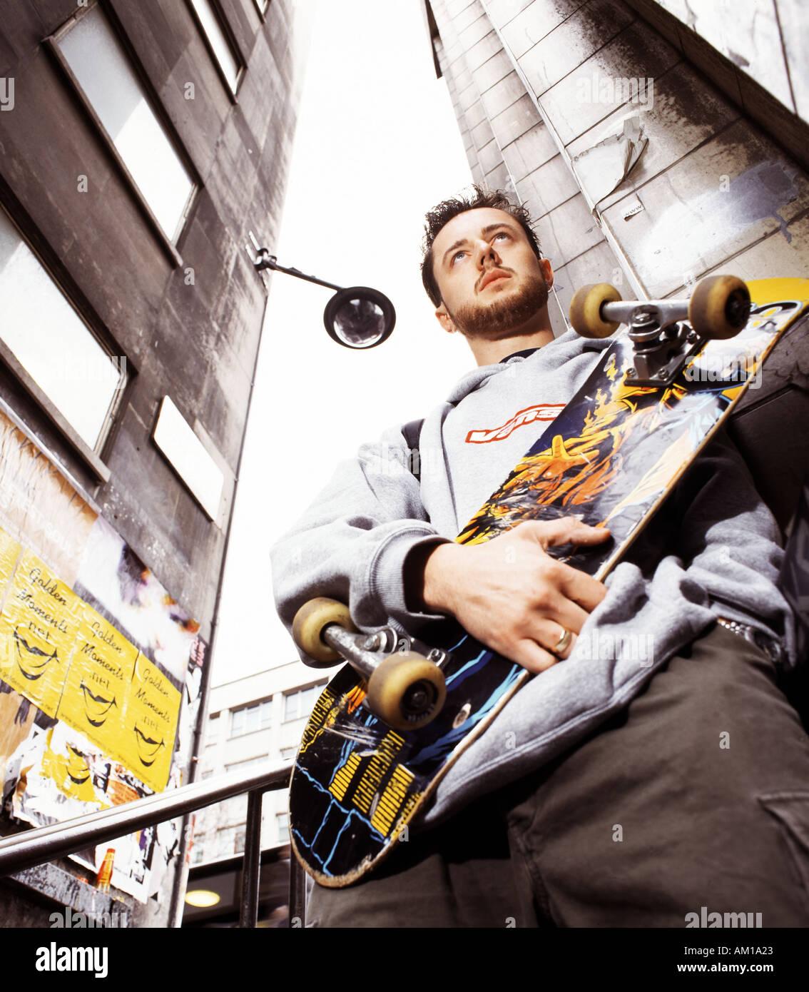 skateboarder holding board posing - Stock Image
