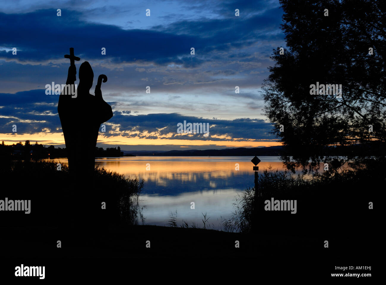 Isle of Reichenau - a silhouette of the statue from the st. pirmin in the dusk - Germany, Europe. - Stock Image