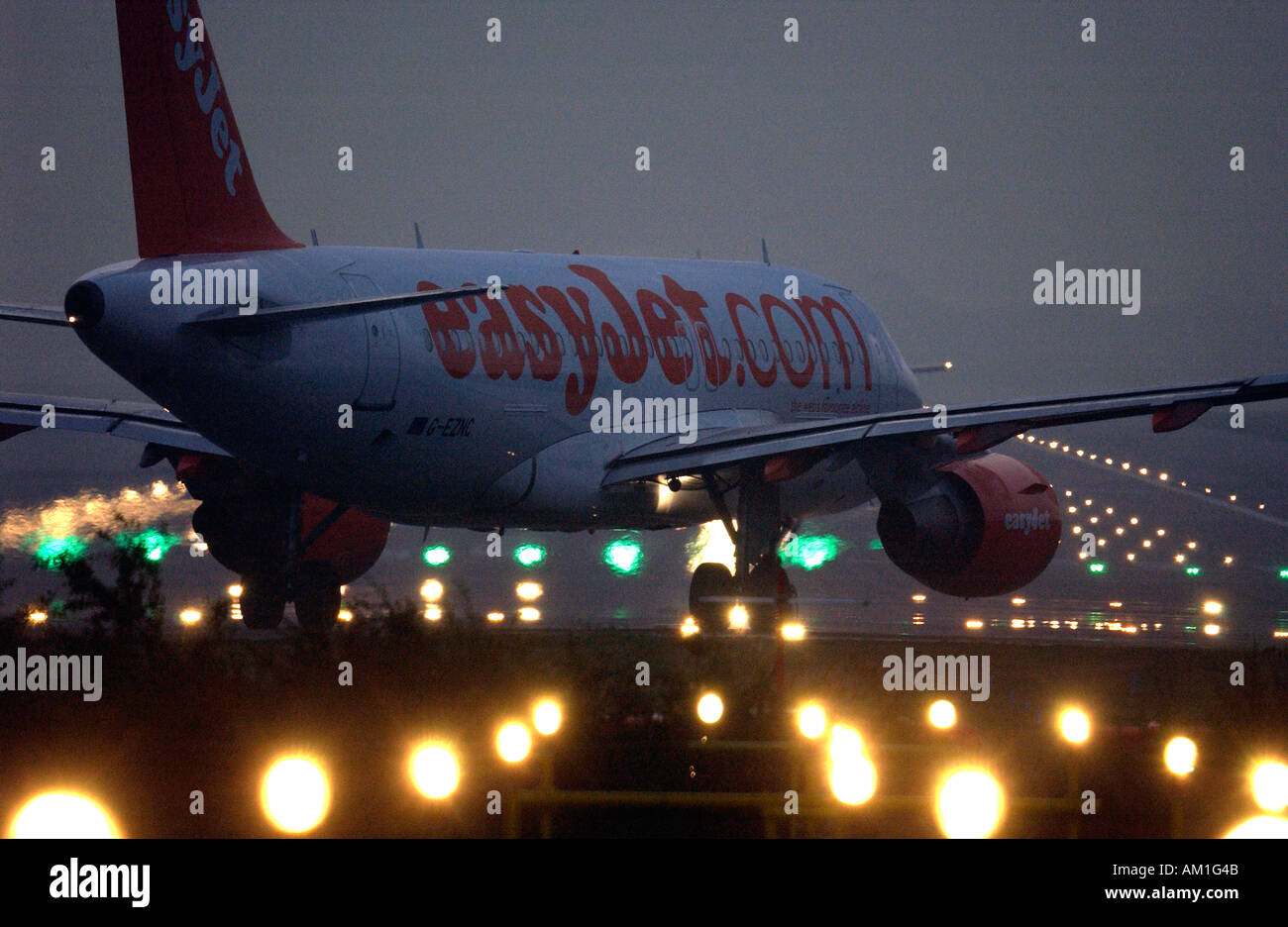 An EasyJet plane prepares for takeoff from London Gatwick airport runway at night - Stock Image