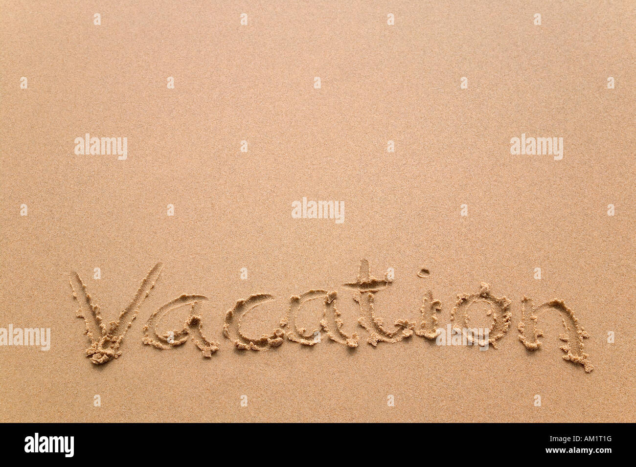 The word Vacation written in sand at the beach - Stock Image