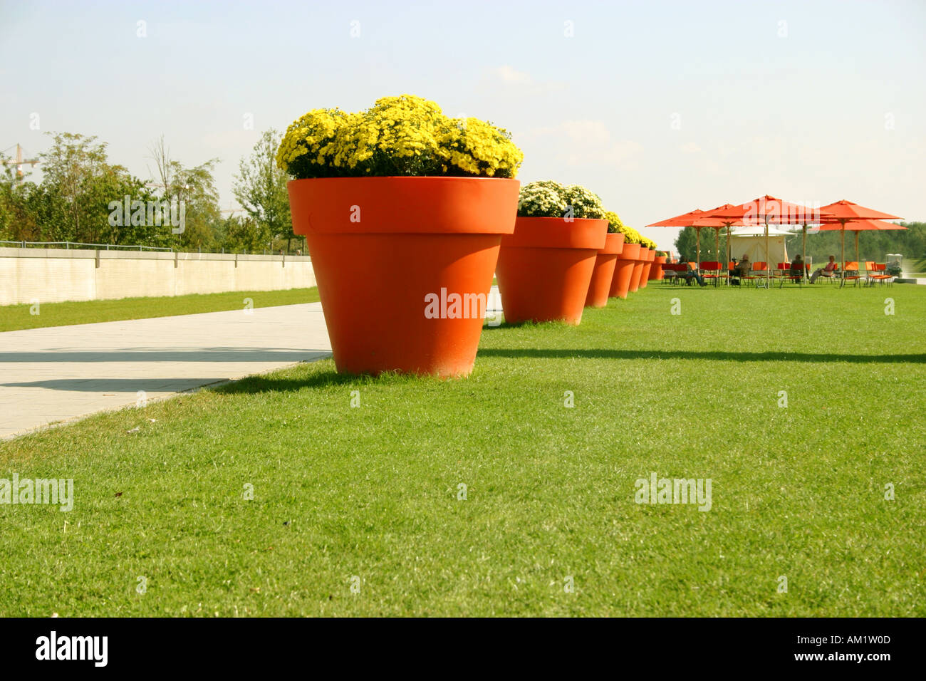 huge orange lifesize flower pots in a row at Federal Garden Exhibition Show 2005 Munich Muenchen Bavaria Germany - Stock Image