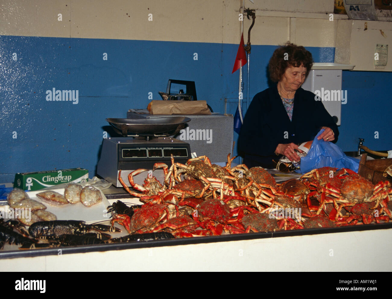 Lady fishmonger selling crabs and lobsters in the Fish Market, St Peter Port, Guernsey, Channel Islands - Stock Image