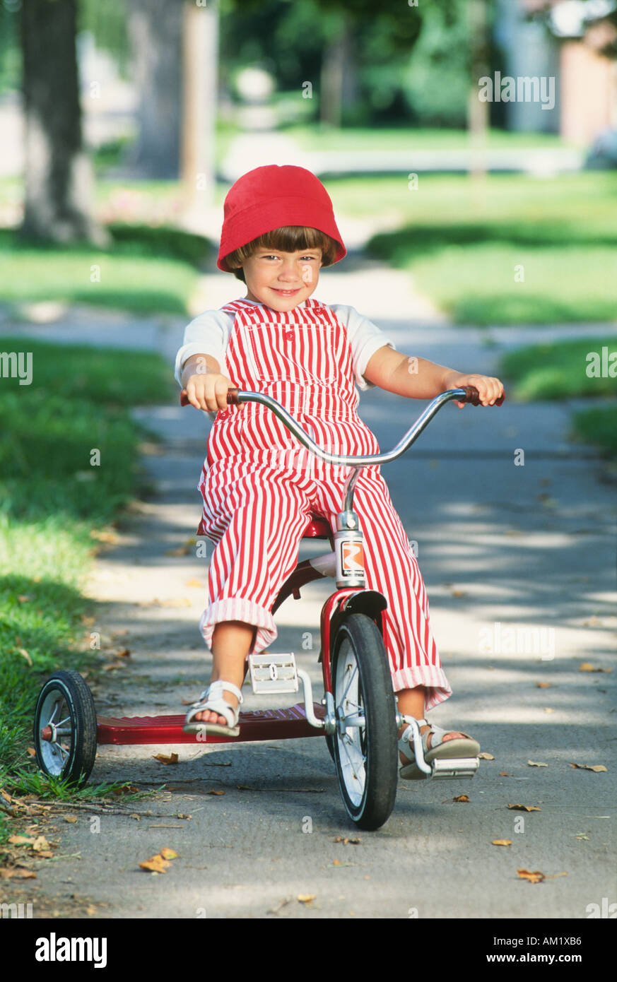 Young girl wearing red hat and striped overalls riding tricycle - Stock Image