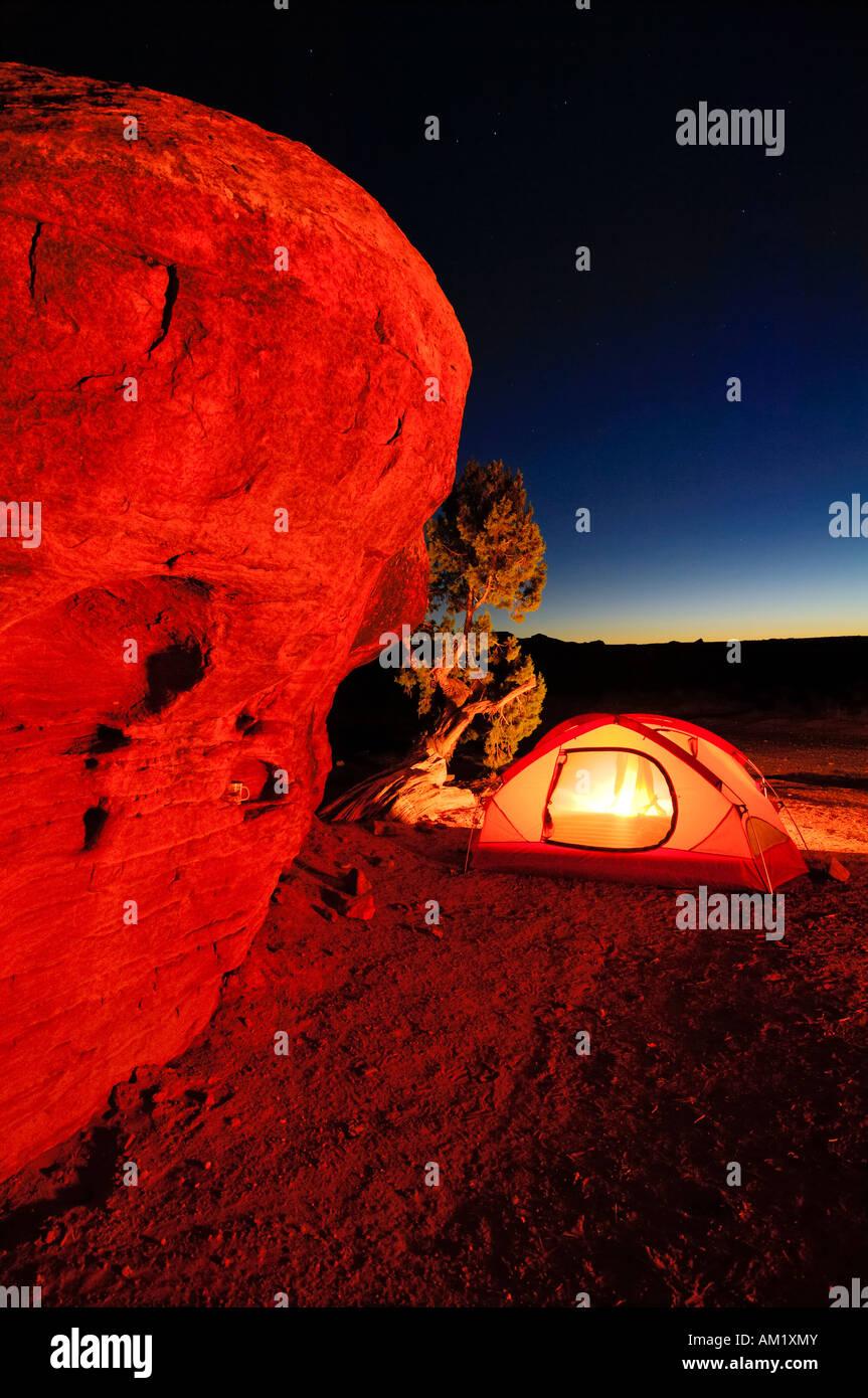 Camp at night with illuminated tent, Canyonlands National Park, Utah, USA - Stock Image