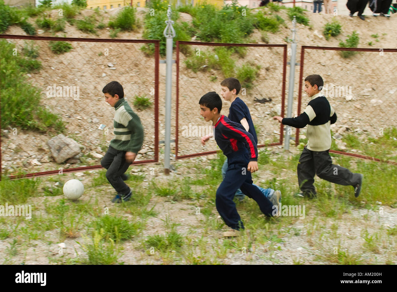 ARMENIA Vanadzor Four school age boys play soccer outdoors in weedy fenced play area run after ball in group - Stock Image