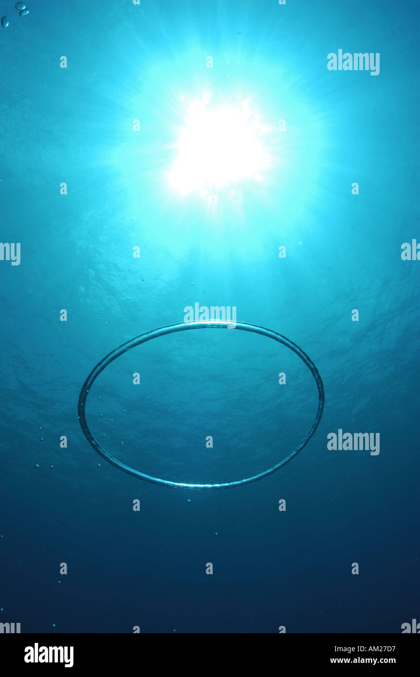 Underwater bubble ring ascending towards the sun - Stock Image