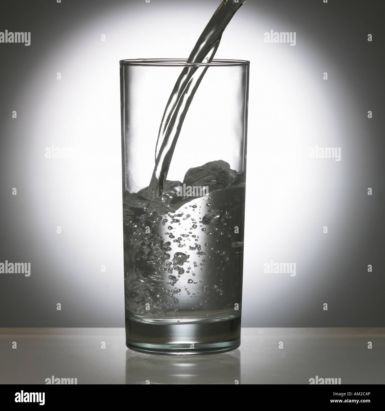 WATER POURING INTO GLASS TUMBLER - Stock Image