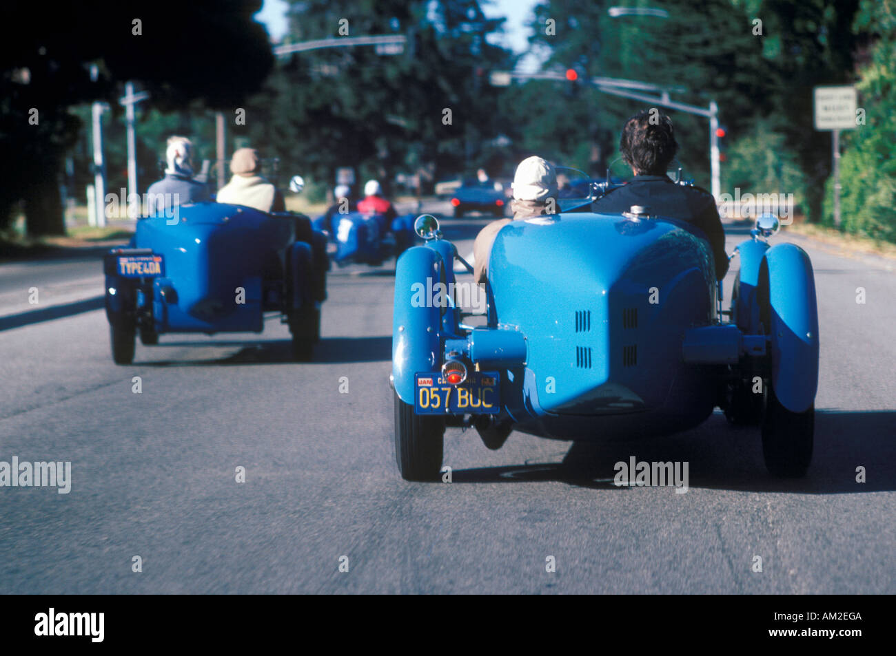 A group of Bugatti owners drive their classic cars down Route 1 ...