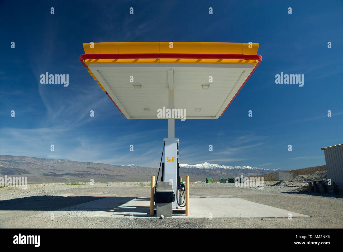 A desolate Shell Gas Station with a sign reading Self on it is Stock