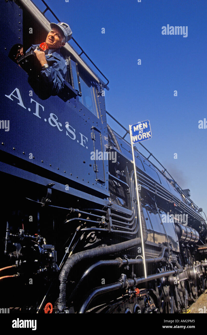 A locomotive engineer waves from the window of an engine of the Atchison Topeka and Santa Fe railroad - Stock Image