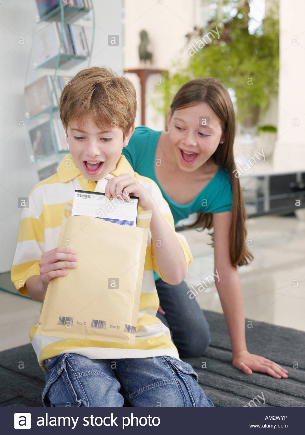 Young boy opening package while girl watches - Stock Image
