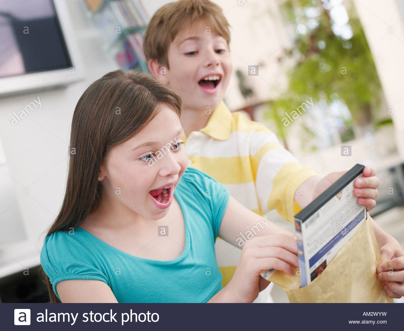Girl opening package while young boy watches - Stock Image