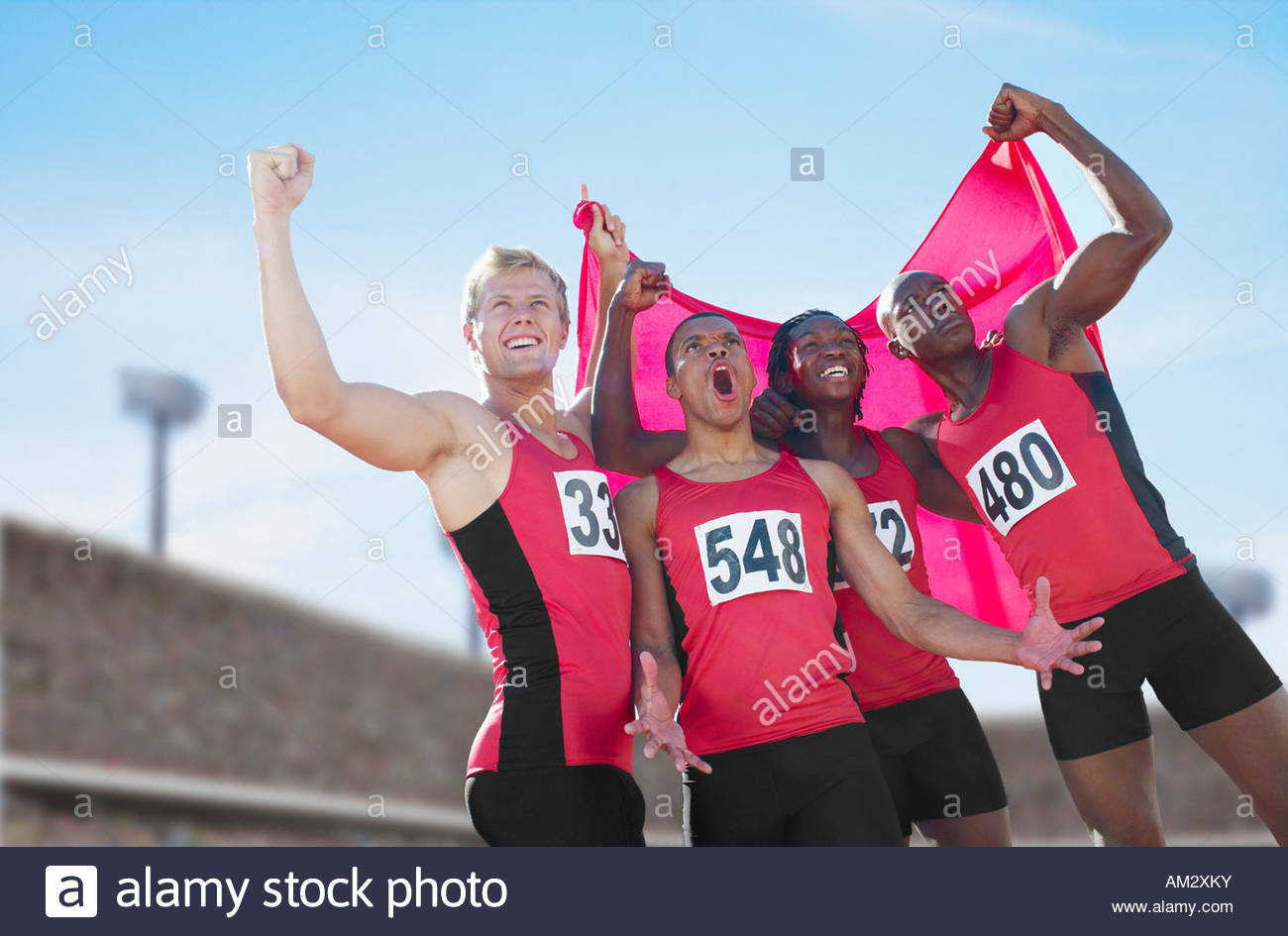 Four athletes cheering together - Stock Image