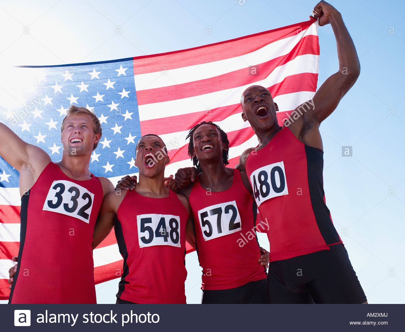Four athletes cheering together with American flag - Stock Image