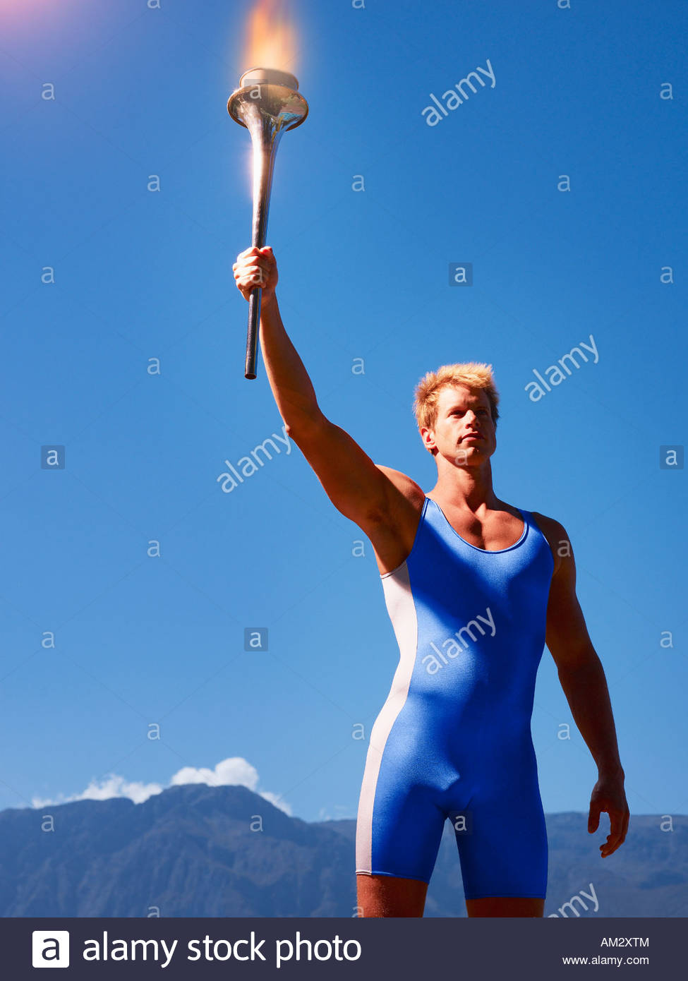 Athlete holding torch in scenic location - Stock Image
