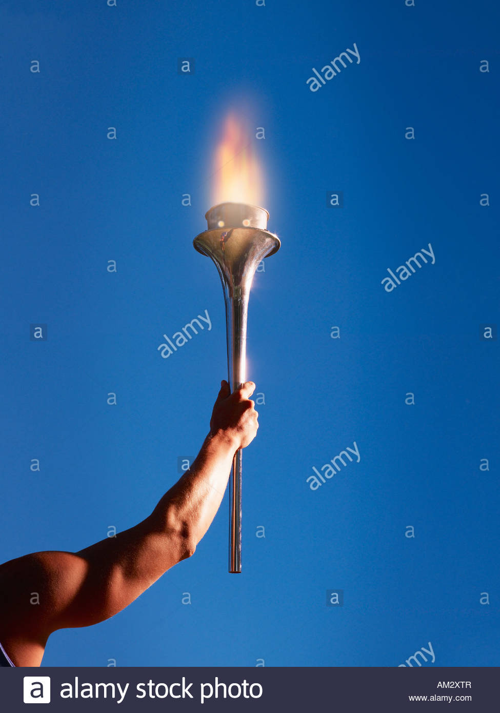Athlete's arm holding up a torch - Stock Image