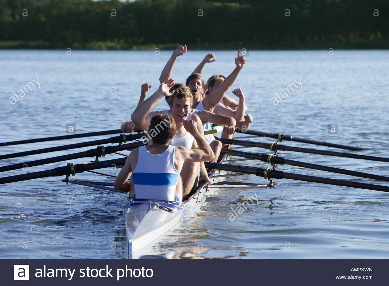 Athletes in a crew row boat cheering - Stock Image