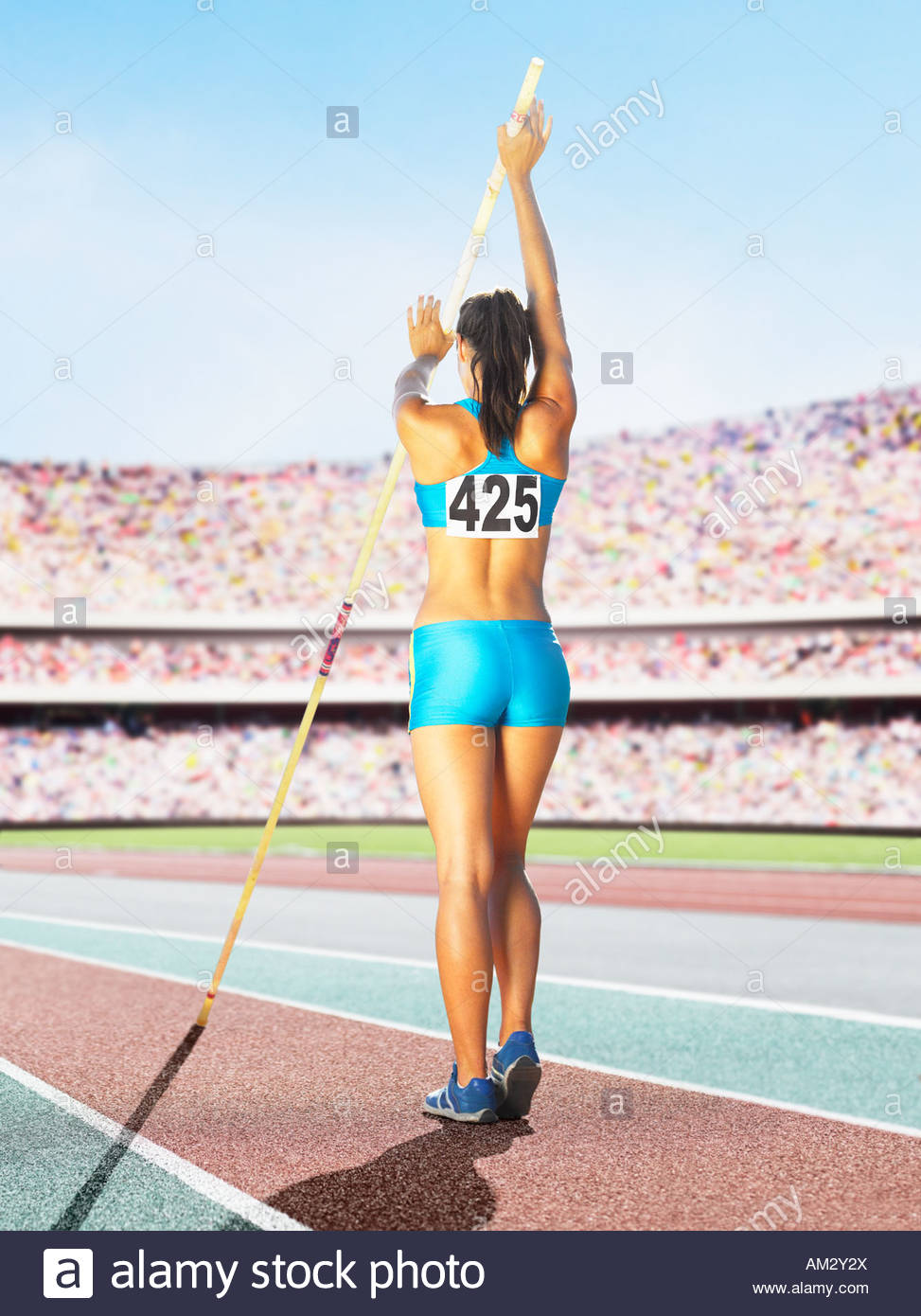 Athlete pole vaulting in an arena - Stock Image