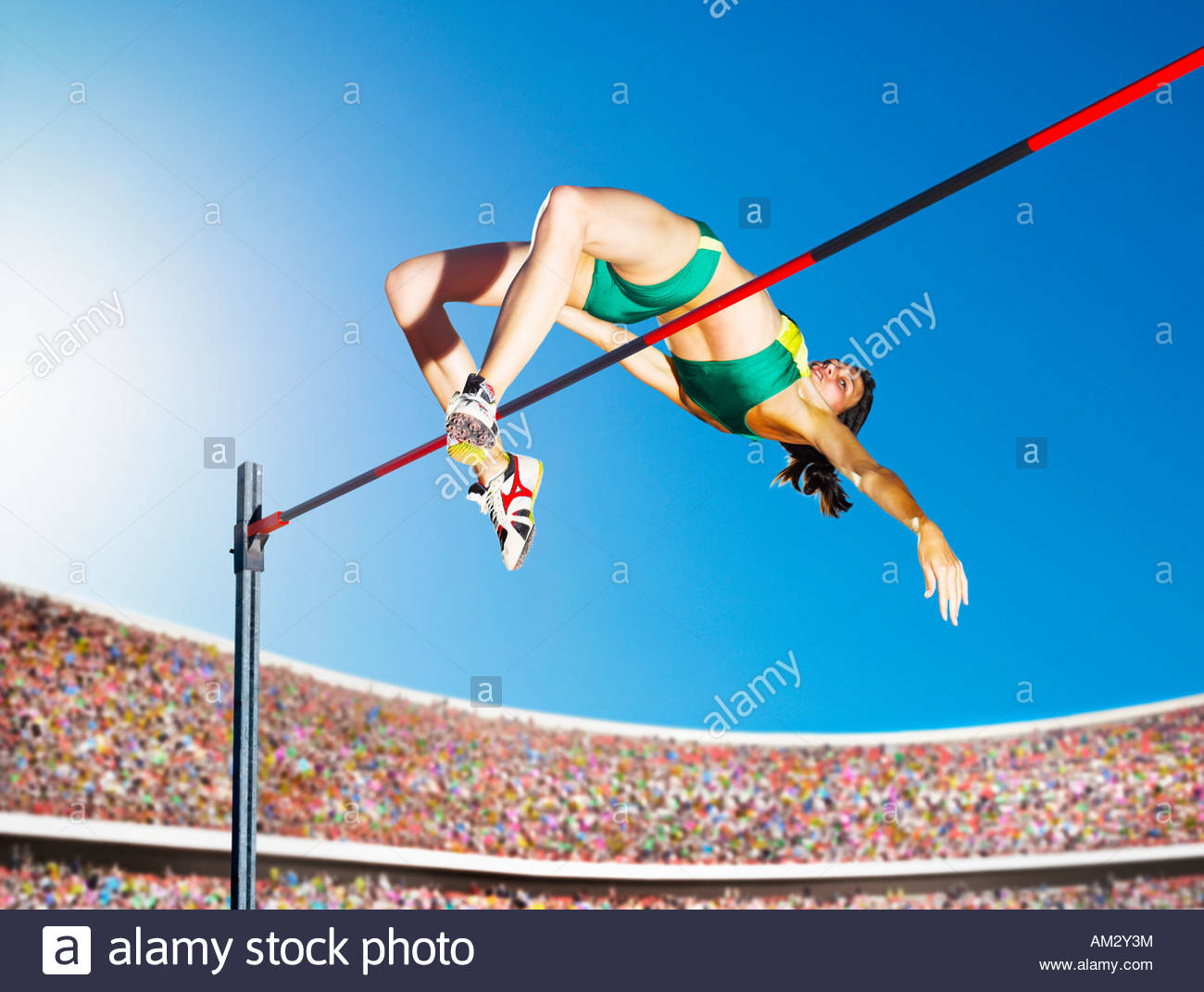 Athlete high jumping in an arena - Stock Image