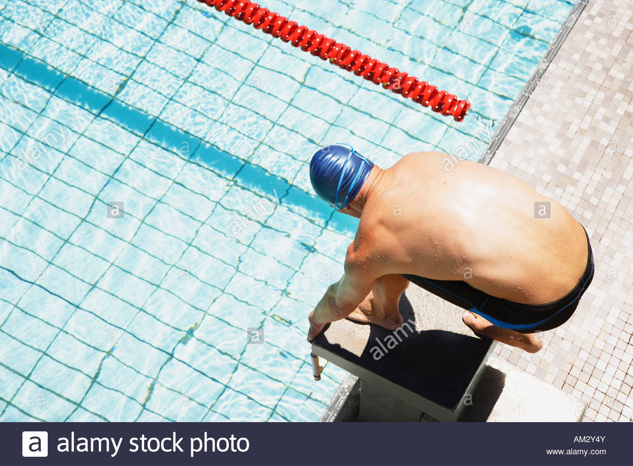 Swimmer on pool start block - Stock Image
