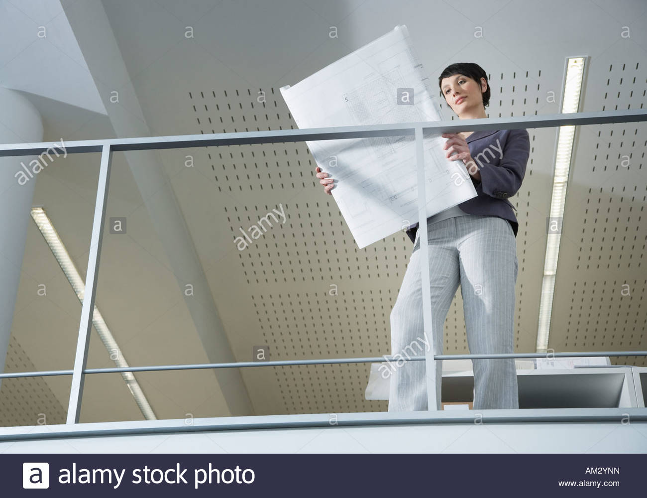 Businesswoman standing with drafts in office - Stock Image